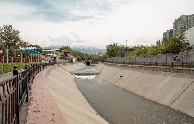 遊歩道のある夏の日の山を背景に市内のダム