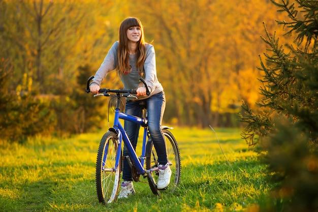 夕暮れの夏の午後に楽しんで公園で自転車に乗ってのんきな笑顔の女性