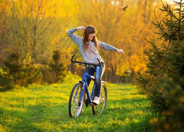 自転車の上に広げられた腕によって幸せな女の子