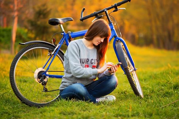 日没で彼女の自転車の隣に座って携帯電話を使用して美しい若い女性