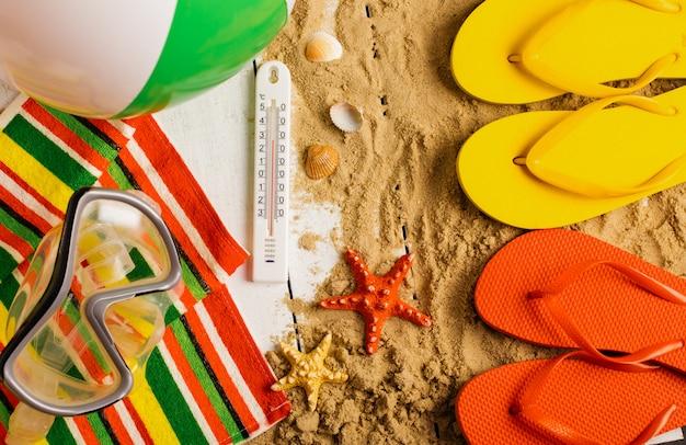 砂浜でビーチサンダル、ボール、貝殻、ヒトデ