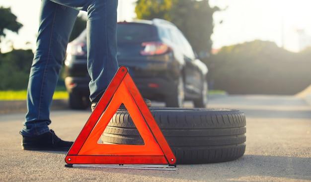 パンクしたタイヤが付いている車の近くに座っている悲しい、落ち込んでいる男