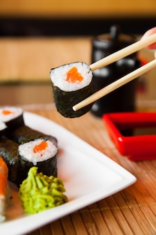 Суши держат палочками и опускают в соус
