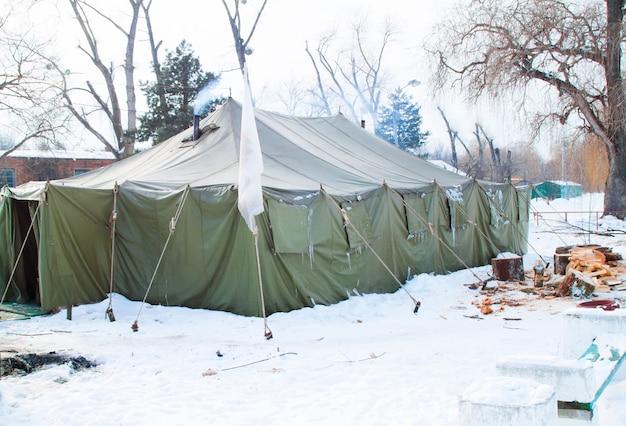 Большая военная палатка и много бревен