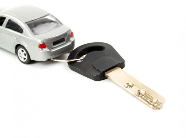 Игрушечный автомобиль и ключ на белом фоне