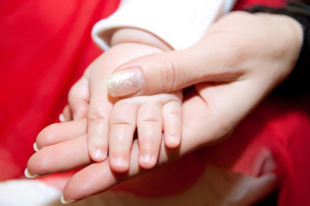 両親の手に赤ちゃんの手のクローズアップ。家族の概念