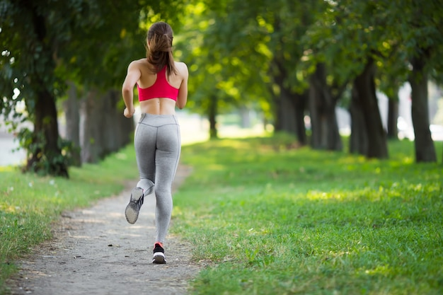 Молодая женщина фитнеса, бегающая в парке.
