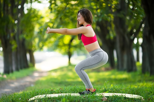 Йога молодой красивой женщины практикуя в зеленом парке.