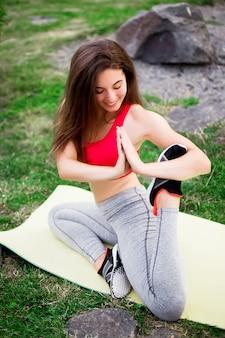 Йога молодой красивой женщины практикуя в зеленом парке около камней.
