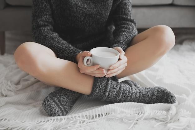 Женщина в уютной комнате с чашкой какао в руке.
