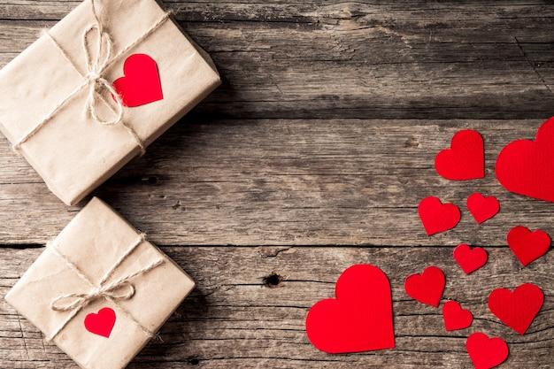 День святого валентина фон. красные сердца, ленты и подарочные коробки на деревянных фоне.