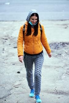 Девушка в медицинской маске с портфелем в оранжевой куртке идет вперед. улыбки