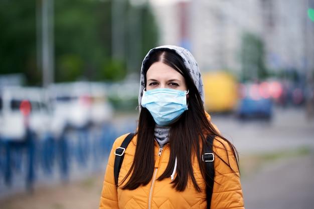 Девушка в медицинской маске, капюшоне и портфеле, дама в оранжевой куртке. ожидает окончания карантина
