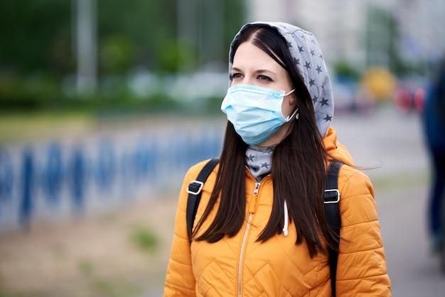 Девушка в медицинской маске, капюшоне и портфеле, с нетерпением жду, в будущее