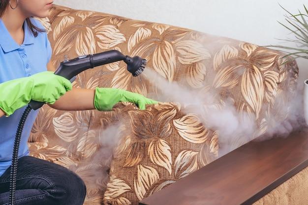 Девушка в зеленых перчатках чистит диван и мебель парогенератором