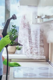 Девушка держит электрический пароочиститель, который очищает кухонный экстракт