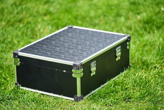 黒いスーツケースは緑の草の上にありました。メタルアングルと強い船体。マジシャンアクセサリー。人はいません。