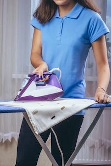 Девушка держит утюг на гладильной доске с паром и гладит вещи
