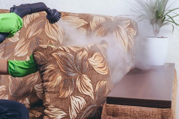 Уборка дома. девушка в зеленых перчатках чистит диван и мебель парогенератором