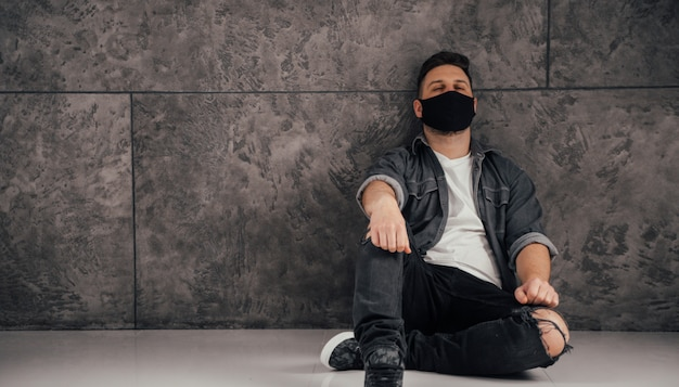 Молодой грустный человек с черной маской в темной комнате молится за мир и коронавирусный карантин
