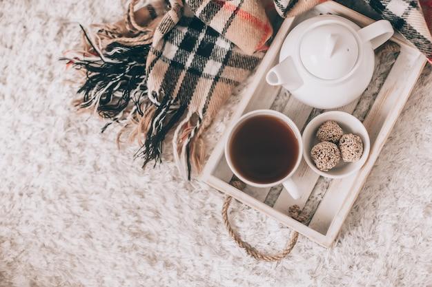 一杯の温かい飲み物とティーポットのサービングトレイ