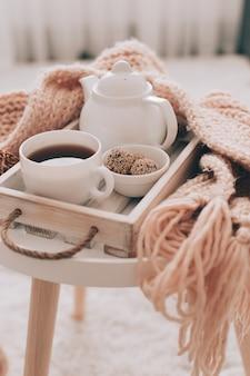 編み物をしたサービングトレイに温かい飲み物とティーポット。