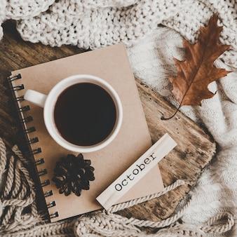 Чашка горячего напитка на ноутбуке и вязание одежды уютная осень или зимняя концепция.