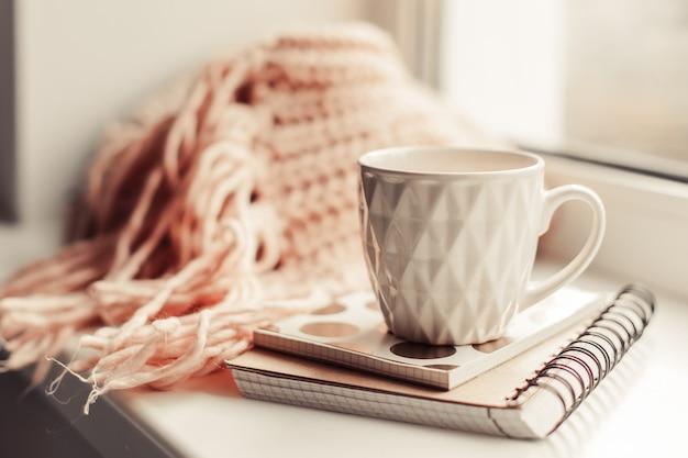 ノートとニットスカーフピンクの気分で美しいピンクのお茶のマグ。
