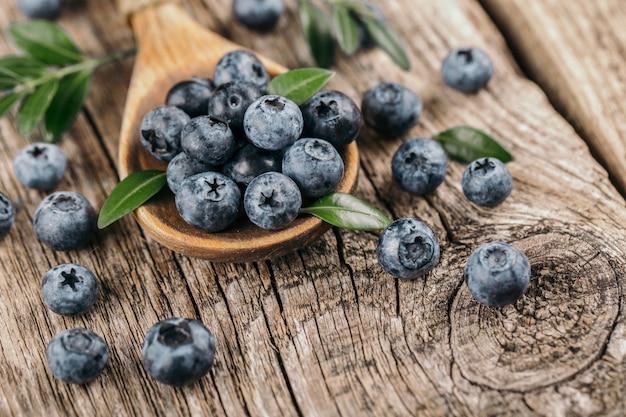 木材の背景に木のスプーンで新鮮なブルーベリー。健康的な食事のコンセプトです。