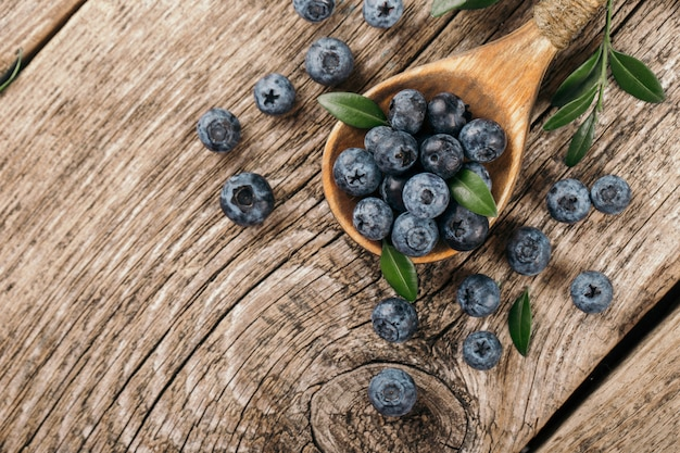 木材の背景に木のスプーンで新鮮なブルーベリー。