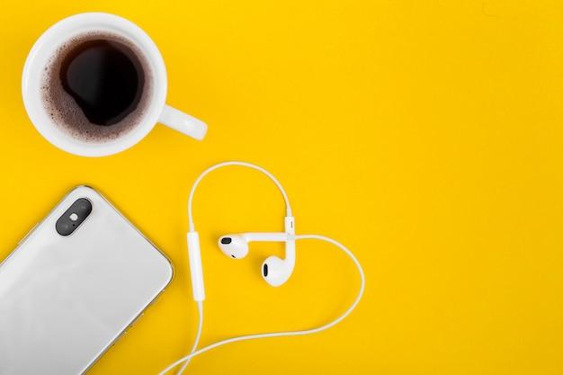 黄色の机の上のハートの形で電話、コーヒー、ヘッドフォンで上から見る。