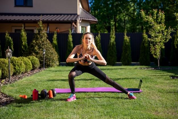 Спортивный тренер фитнес женщина разминки перед тренировкой онлайн в саду