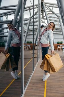 長い白パンバゲットと食料品の買い物紙袋を歩いて、コーヒーカップを保持している若い女性を笑顔