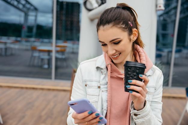 ショッピングとコーヒーカップを保持した後、スマートフォンを使用してタクシーに乗る笑顔の若い女性