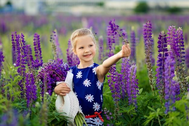 Портрет конца-вверх маленькой милой девушки с светлыми волосами играет на цветя поле люпина. концепция детства. дети и природа.