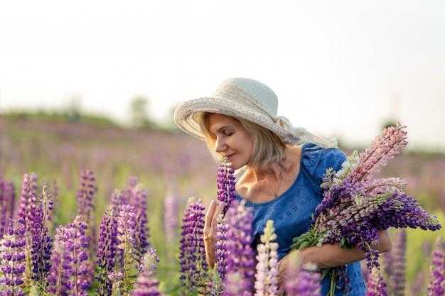 開花ルピナスフィールドの帽子で幸せな中年女性の肖像画。女性の幸福の概念。