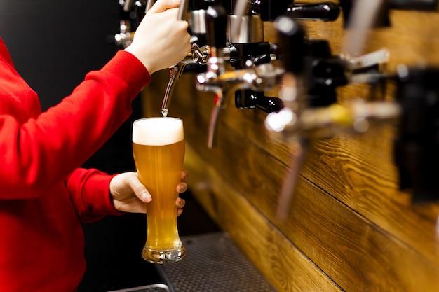 Рука бармена наливает большое светлое пиво в кране