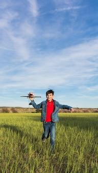 Мальчик работает с самолета в парке.