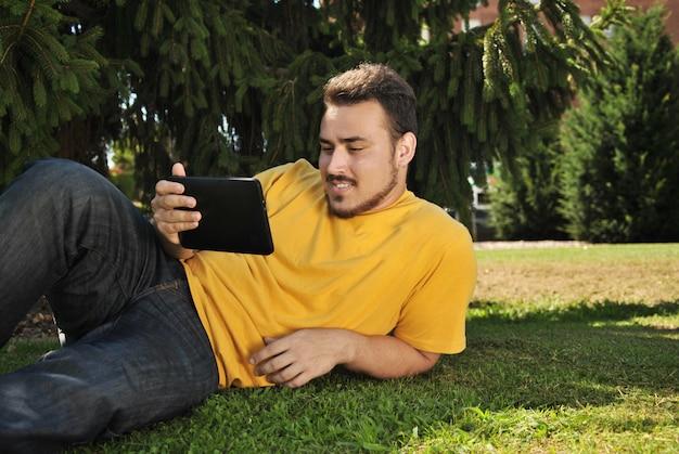 タブレットで太陽の下で草の上に横たわる大学生