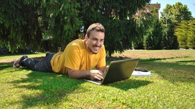 太陽の下で草の上に横たわる大学生