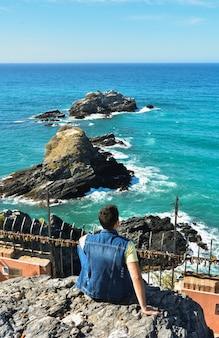 地中海のいくつかの岩の景色を考えている男。