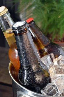 木のテーブルにさまざまなビール。それらを冷たく保つために氷が付いているびんそしてガラスがあります