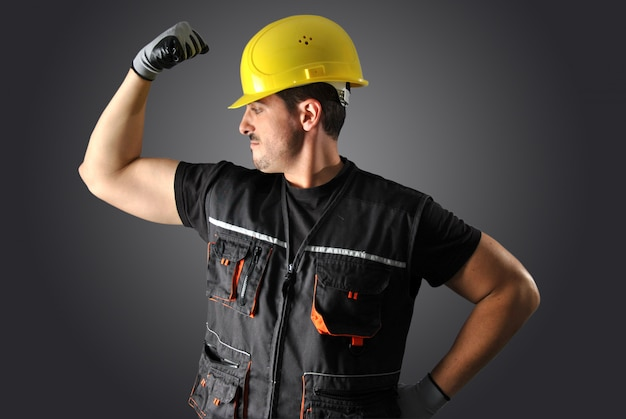 黄色いヘルメットと顔がおかしい労働者