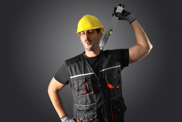 黄色いヘルメット、ドリル、ハンマーの労働者