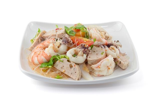 Салат из морепродуктов в тайском стиле с лапшой на белом фоне