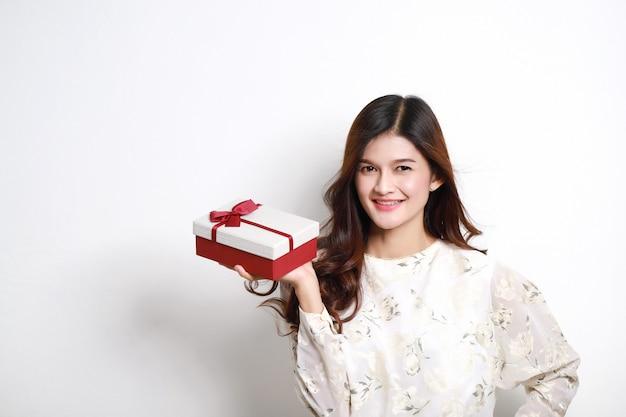 Портрет счастливой усмехаясь азиатской девушки в платье держа присутствующую коробку, красивую тайскую девушку с подарочной коробкой.