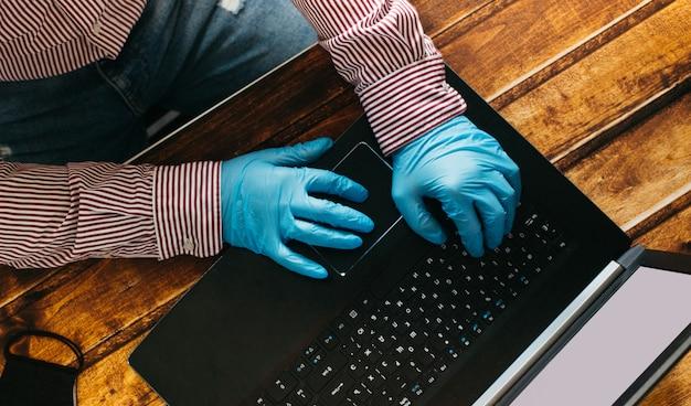 自宅で保護のために使い捨て手袋を着用したラップトップで作業する男性。コロナウイルスアウトブレイク。隔離されたビジネスマン。在宅勤務。家にいる。
