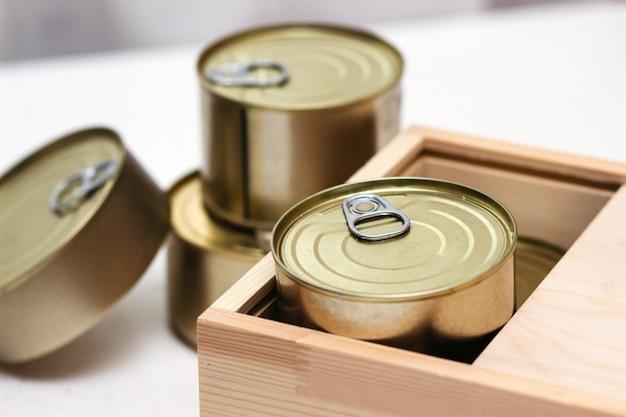 Жестяные банки в коробке. разнообразие консервов в полных жестяных банках. настоящие консервы. вид сверху. выборочный фокус.