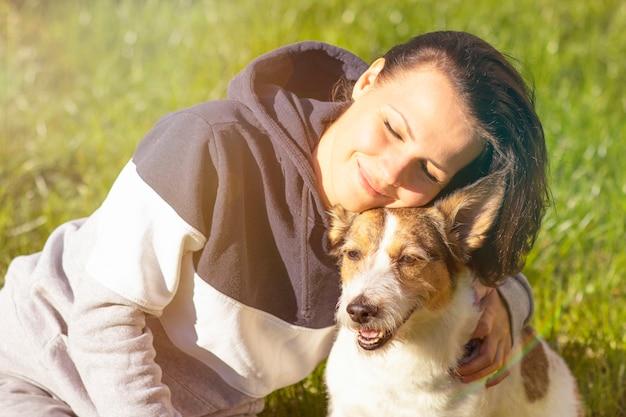 屋外笑みを浮かべて彼女の犬を持つ女性