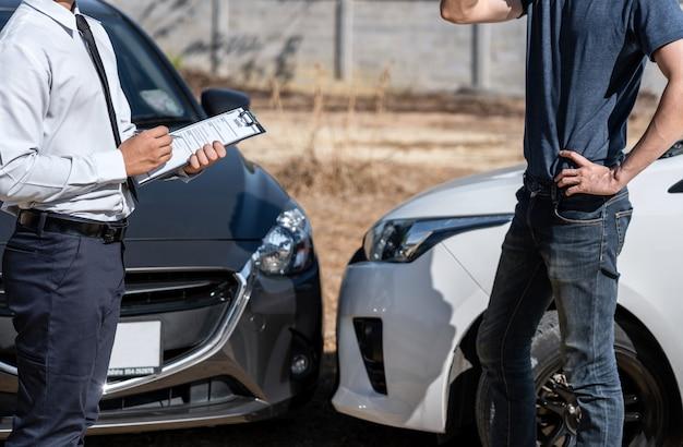 保険代理店と顧客は、事故の衝突、交通事故、保険のコンセプトの後、交渉、チェック、レポート請求フォームプロセスへの署名を評価しました